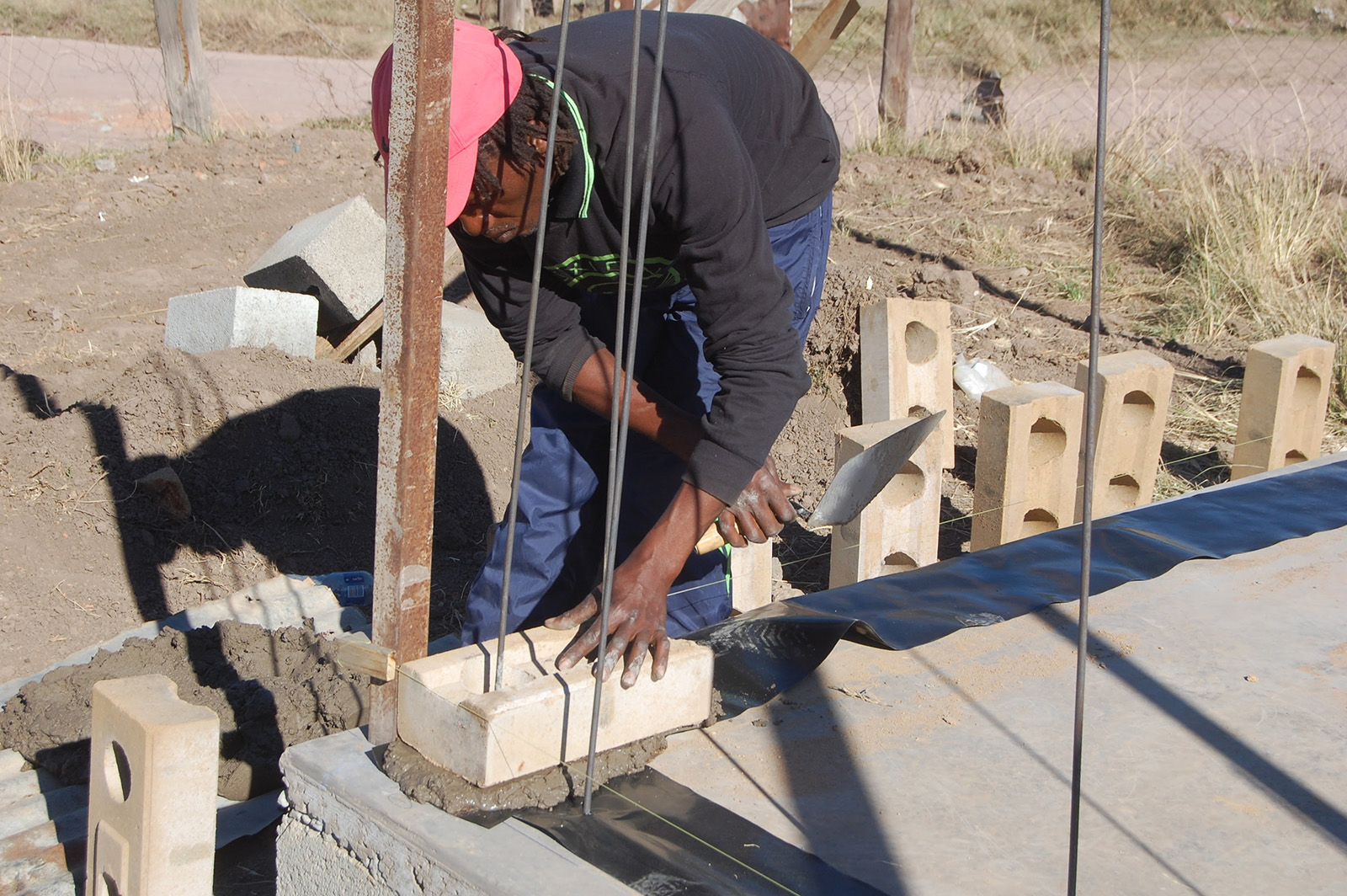 Compressed earth block building construction with damp proof course